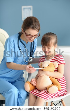 Doctor checking little girl's temperature - stock photo