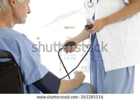 Doctor checking senior patient blood pressure - stock photo