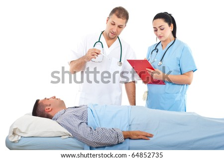 Doctor checking temperature to a sick patient in bed and  nurse writing in clipboard  in a hospital - stock photo