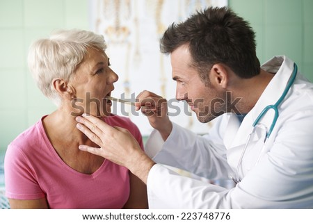 Doctor checking throat of senior woman  - stock photo