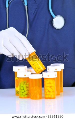 Doctor choosing prescription bottle from many others - stock photo