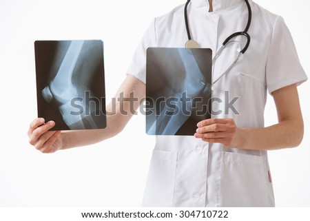 Doctor comparing X-rays with each other, white background - stock photo