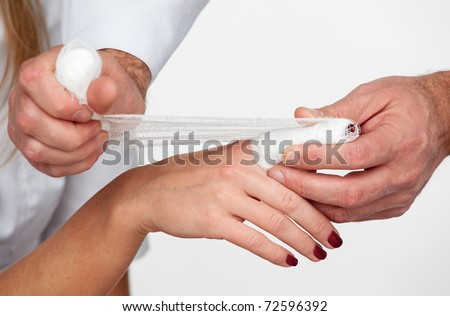 Doctor cover the finger of patient by bandage isolated on a white background - stock photo