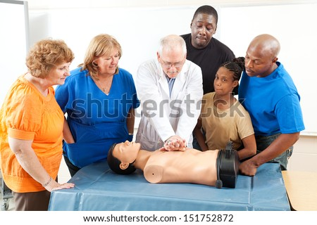 Doctor demonstrates CPR for and adult education class on first aid.   - stock photo