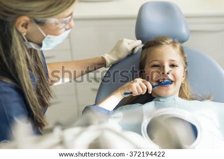 Doctor dentist teaching a child to brush teeth. - stock photo