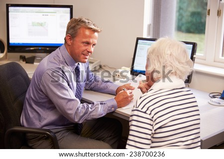 Doctor Discussing Test Results With Senior Female Patient - stock photo
