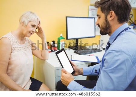 Doctor discussing with patient over digital tablet at the hospital