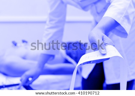 doctor does electrocardiogram for patient, blue toning - stock photo