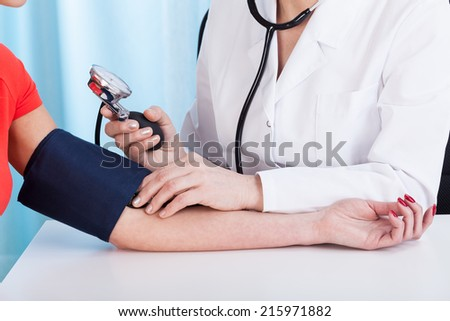 Doctor doing professional pressure examine her young patient - stock photo