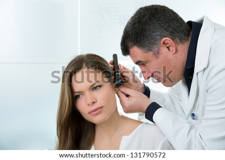 Doctor ENT checking ear with otoscope to woman patient at hospital - stock photo