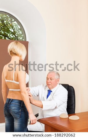 doctor examine woman waist measure with tape, plastic surgery - stock photo