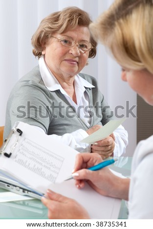 Doctor examines results of blood tests of elderly patient - stock photo
