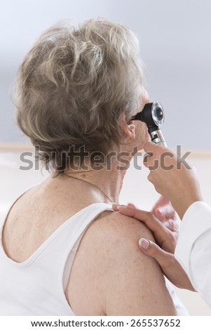 doctor examining elderly patient's ears - stock photo