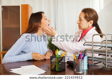 Doctor examining girl patient at home - stock photo