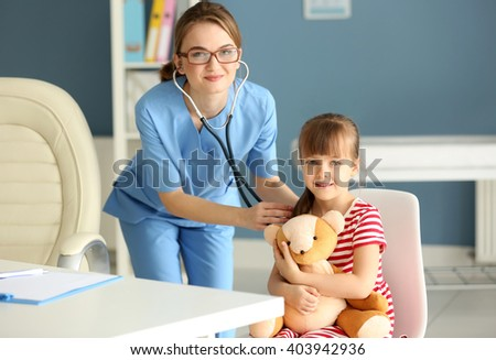 Doctor examining girl with stethoscope in the office - stock photo