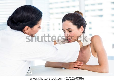 Doctor examining her patients neck in medical office - stock photo
