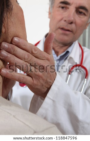 Doctor examining his patient's glands