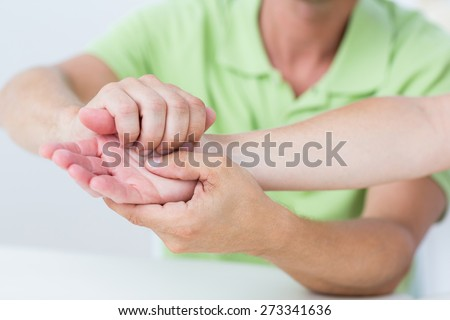 Doctor examining his patients hand in medical office - stock photo
