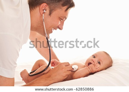 doctor examining newborn on a white - stock photo