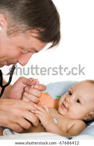doctor examining newborn on a white