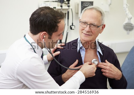 Doctor Examining Senior Male Patient In Hospital - stock photo