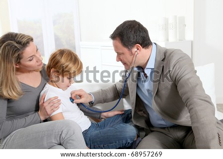 Doctor examining sick little boy - stock photo