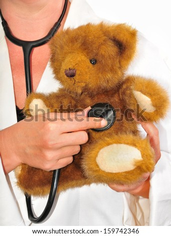 doctor examining with a stethoscope to a teddy bear - stock photo
