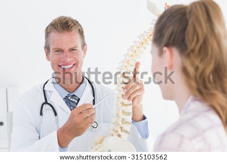 Doctor explaining anatomical spine to his patient in medical office - stock photo