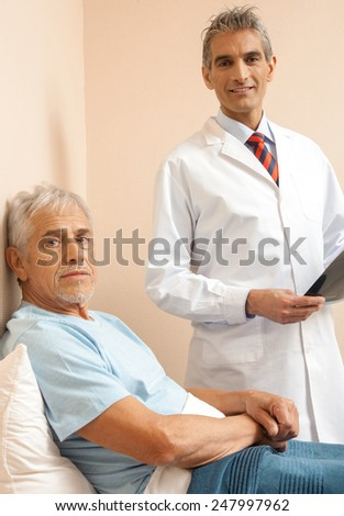 Doctor explaining medical test to male patient in 60s. Happy scan test. - stock photo