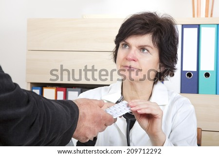 Doctor explaining patient's tablets - stock photo