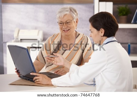 Doctor explaining results to senior patient in office, using laptop computer.? - stock photo