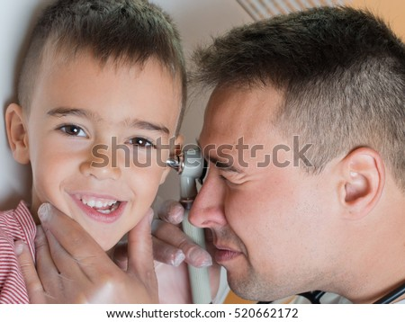 Doctor explores the ear to child close up