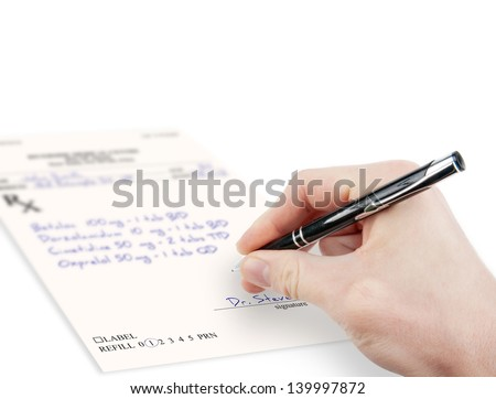 Doctor filling in medical prescription - stock photo