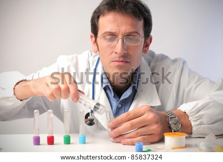 Doctor filling some test tubes with a syringe - stock photo