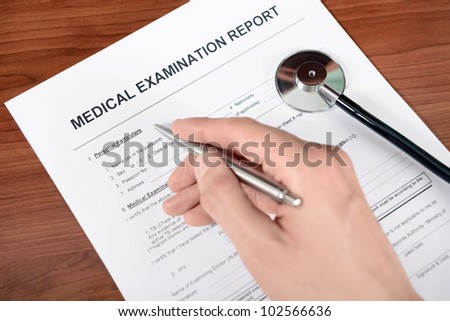 Doctor fills out blank medical report form. - stock photo