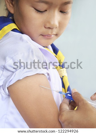 Doctor gives injection to young female student arm. - stock photo