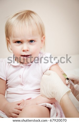 Doctor giving a child an intramuscular injection in arm - stock photo