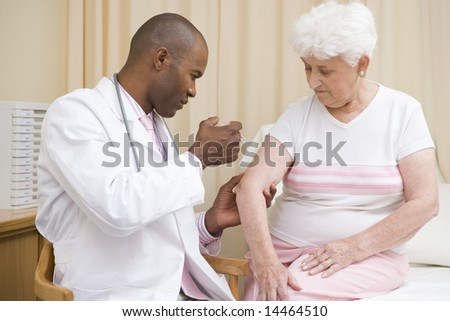 Doctor giving needle to woman in exam room - stock photo