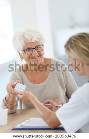 Doctor giving pills to elderly woman