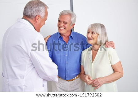 Doctor greeting happy senior couple with a handshake in a hospital - stock photo