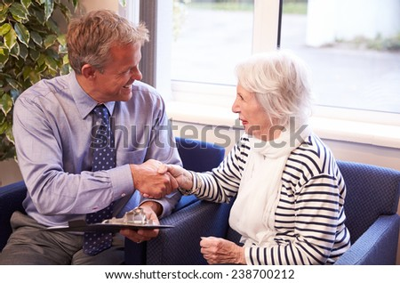 Doctor Greeting Senior Female Patient With Handshake - stock photo