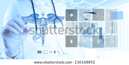 doctor hand draws Caduceus on the new computer interface - stock photo