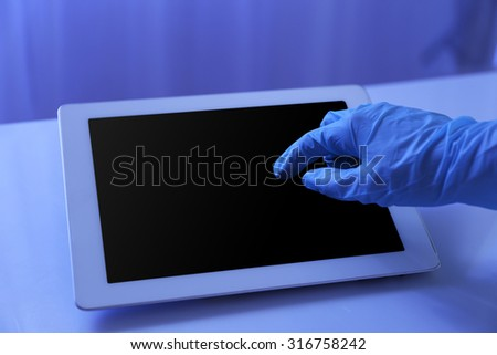 Doctor hand in rubber glove using tablet in office - stock photo