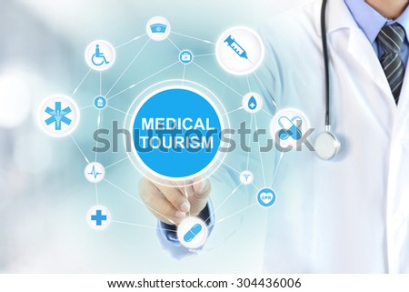 Doctor hand touching MEDICAL TOURISM sign virtual screen - stock photo