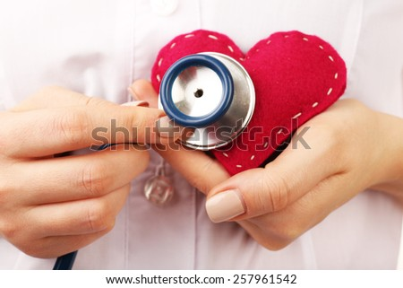 Doctor hands with heart and stethoscope, closeup