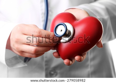 Doctor hands with stethoscope and red heart, closeup - stock photo