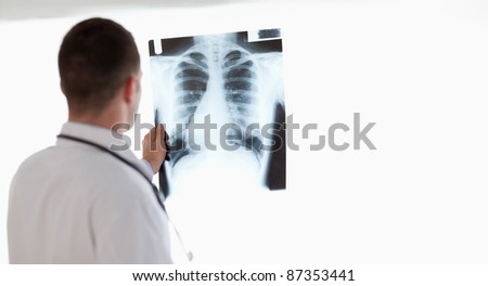 Doctor having a close look at x-ray image while holding it against light - stock photo