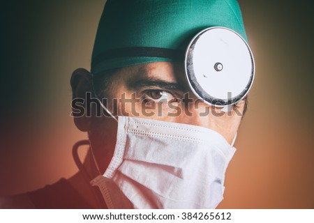 Doctor Head Mirror. Physician wearing scrubs, surgical mask and head mirror, portrait. - stock photo