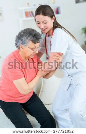 Doctor helping an old lady to stand - stock photo