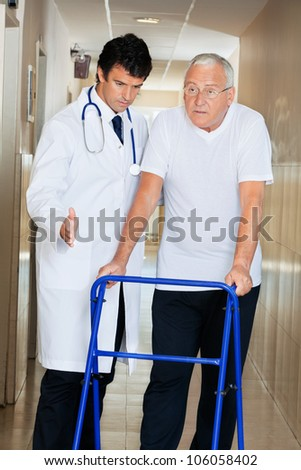 Doctor helping senior patient walk down hallway using Zimmer frame - stock photo